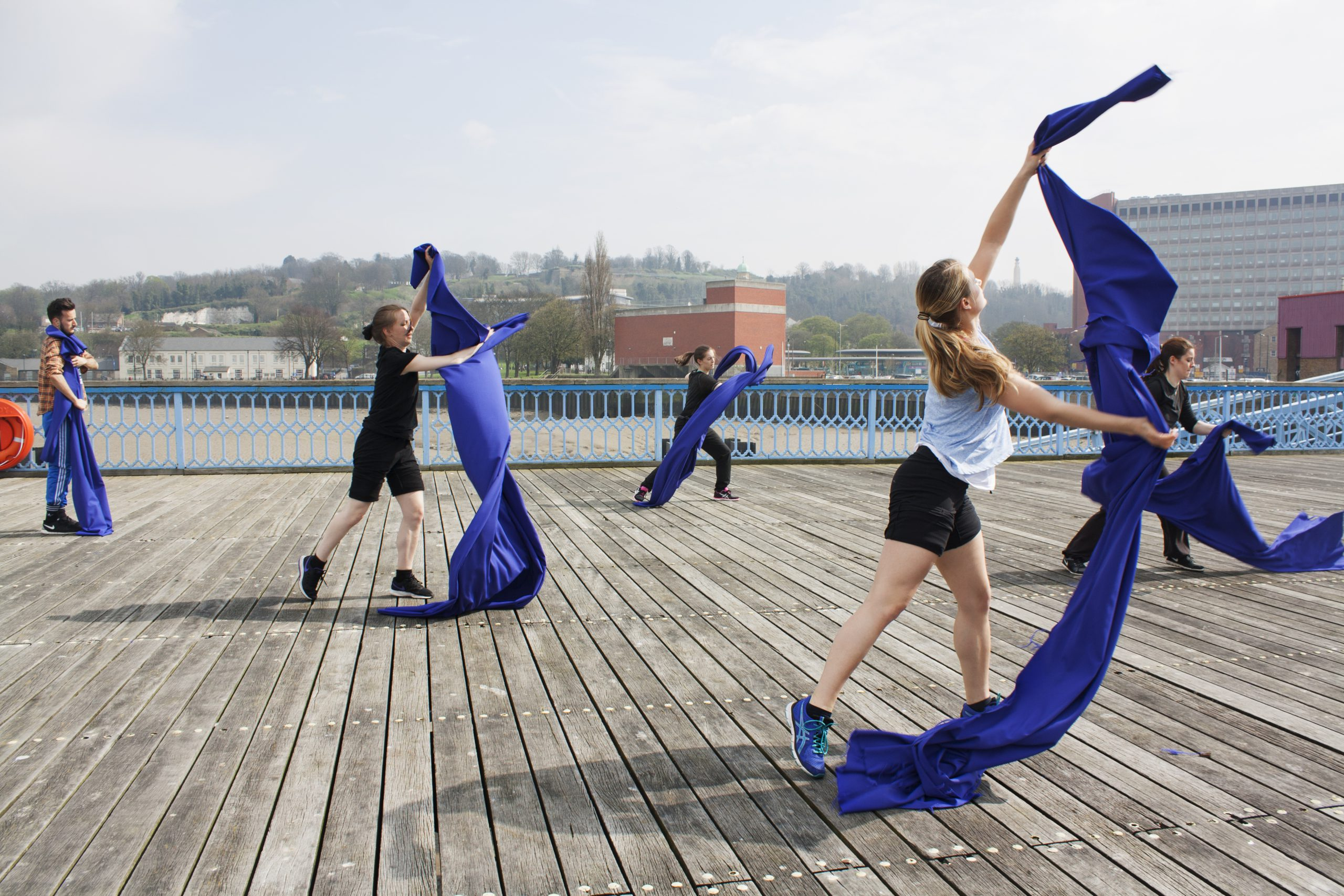 Dancers with cloth on pier