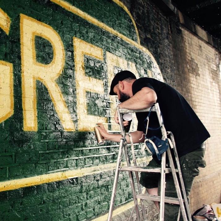 artist spray painting mural art work under station bridge