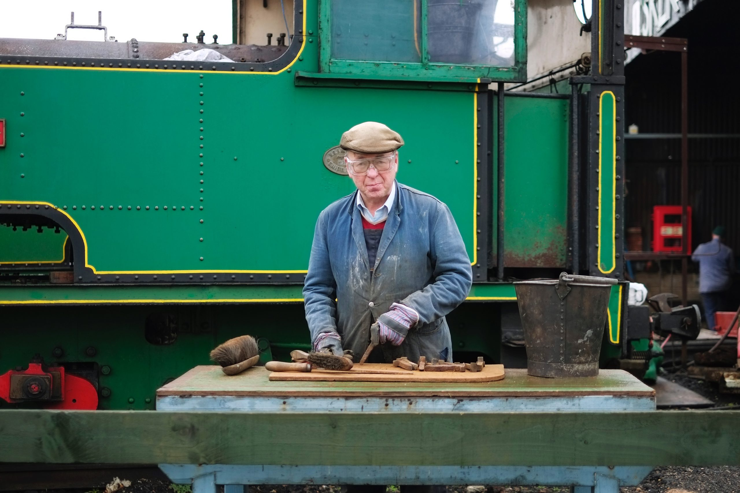 train enthusiast mending parts looking straight to camera