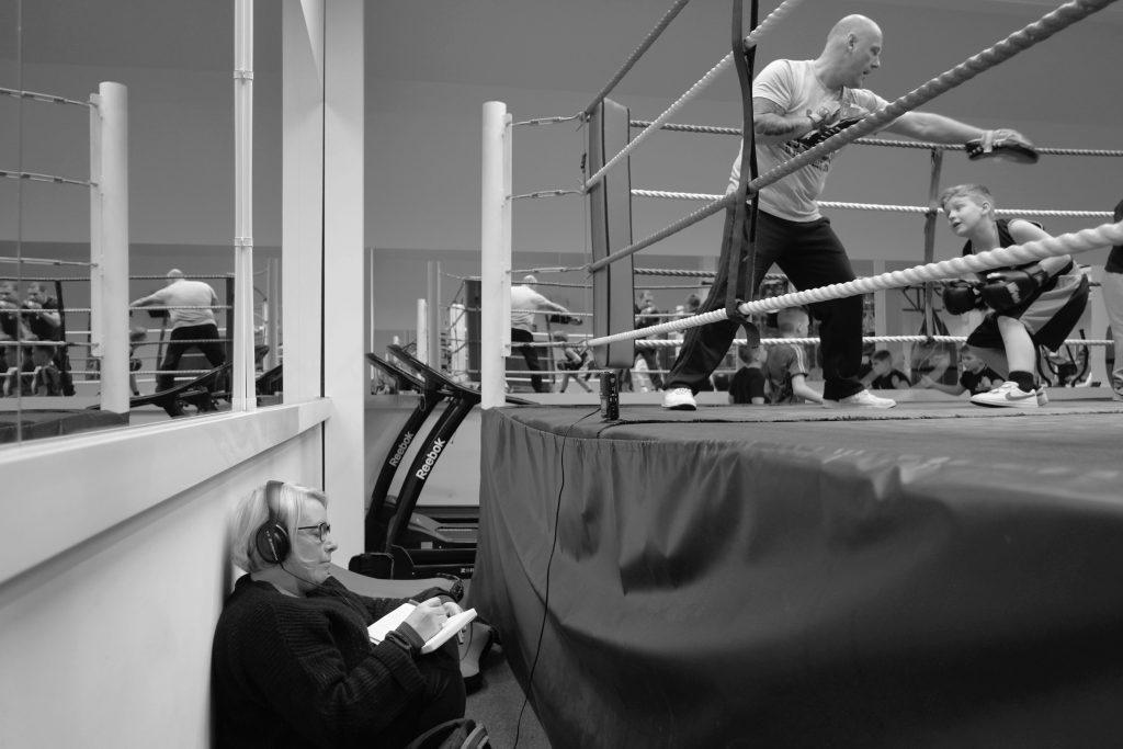 Jane Pitt sat next to boxing ring wearing headphones and taking notes