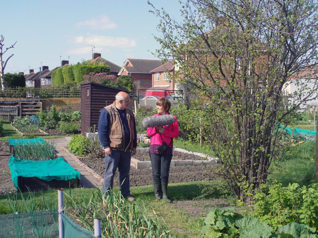 Kate Chapman with recording equipment standing outside with allotment holder
